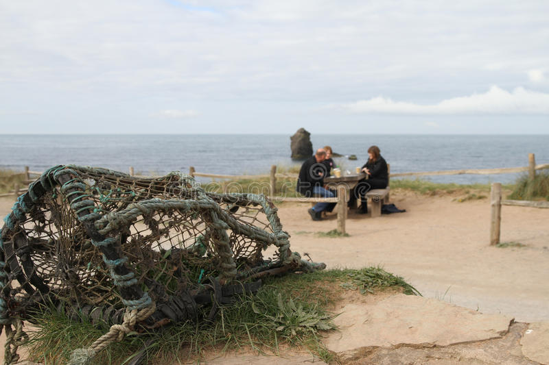 Lobster pot and people by Thurlestone rock Devon. Lobster pot in focus with people having tea blurred in the background against the sea and sky royalty free stock photos