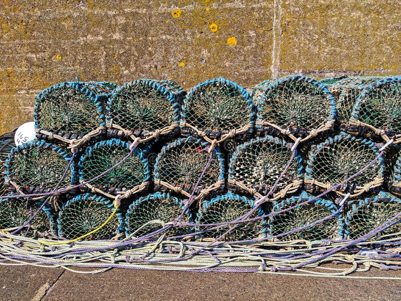 Empty lobster pots stacked up on the harbourside royalty free stock image