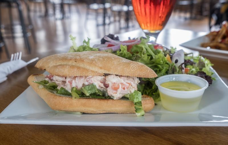 Lobster Roll Served with Fresh Green Salad in a Restaurant stock photo