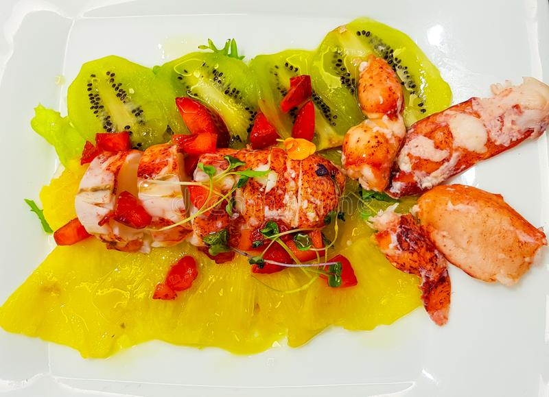 lobster salad with lobster and a bed of strawberries kiwis and pieces of pineapple stock images