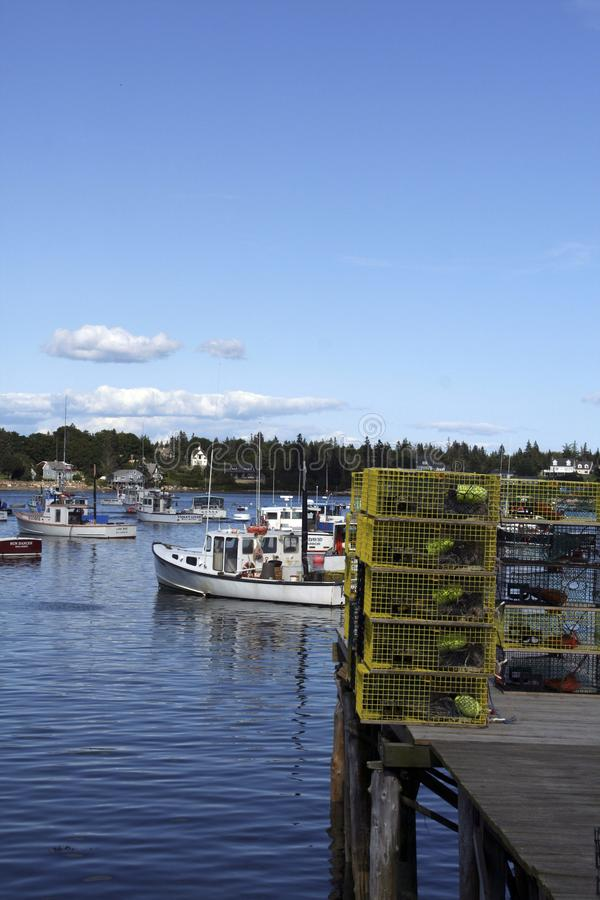 Lobster traps on wharf and lobster boats royalty free stock image