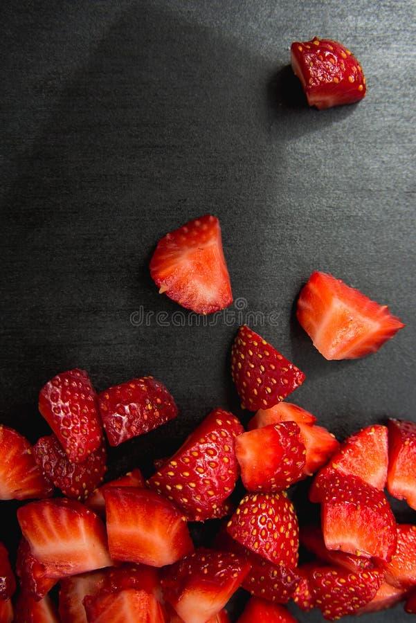 Lobule sliced strawberries. On black slate background royalty free stock photos