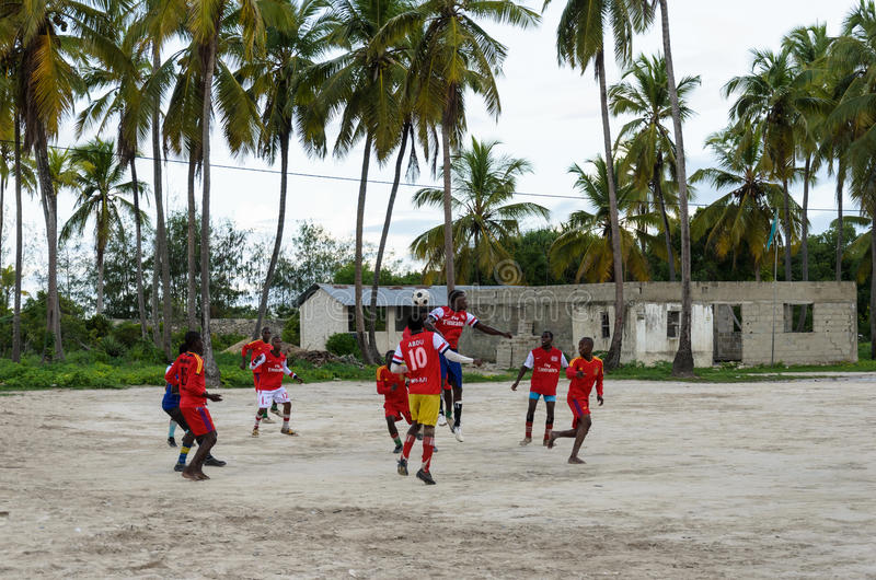 Local african soccer team during training on sand playing field. ZANZIBAR, TANZANIA - MARCH 26 2013: local african soccer team during training on sand playing stock image