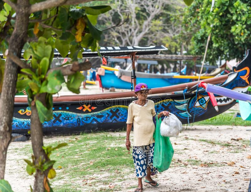 Local aged female Balinese collecting garbage along the foreshore stock images