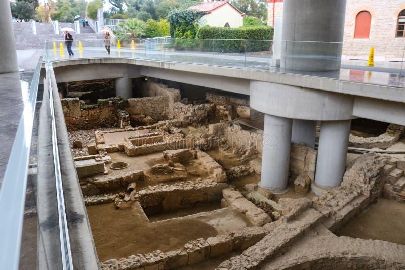 Local arqueológico abaixo da entrada principal ao museu da acrópole com os turistas na chuva Atenas Grécia 01 04 2018 fotos de stock royalty free