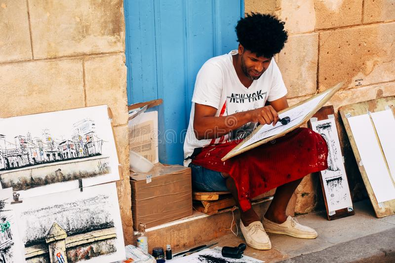 A local artist paints for tourists in Havana, Cuba. A local artist paints a painting with a roller for tourists in Havana, Cuba stock photos