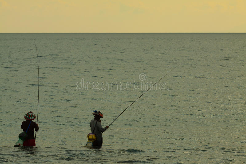 Local Asia mans fishing in the sea with fair sun light early morning at sunrise time royalty free stock photo