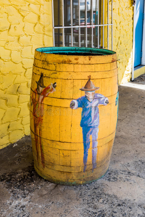 Local Caribbean design on the public trash receptacles. Yellow barrel against yellow stone wall stock photography