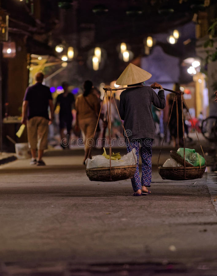 Local carrying produce with carrying pole in Hoi An stock photos
