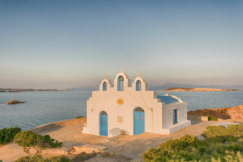 Local church in Pirgaki in Paros island against the blue Aegean sea. A beautiful landscape. royalty free stock image