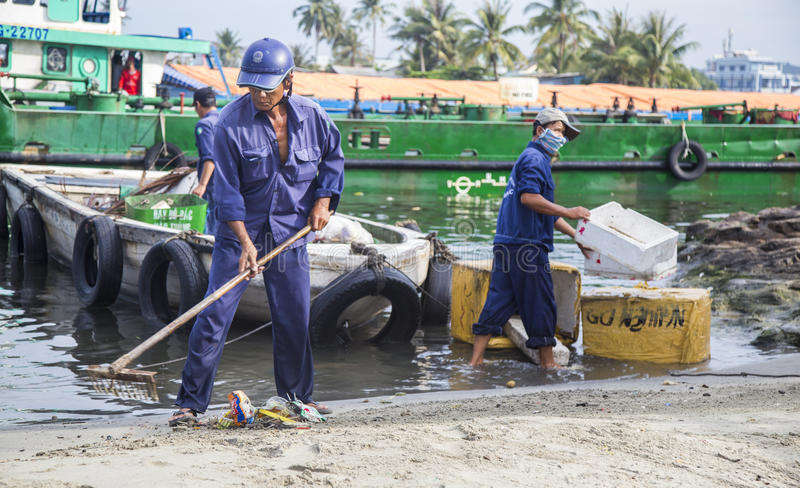 Local cleaners cleaning and carrying garbage on the beach royalty free stock photography