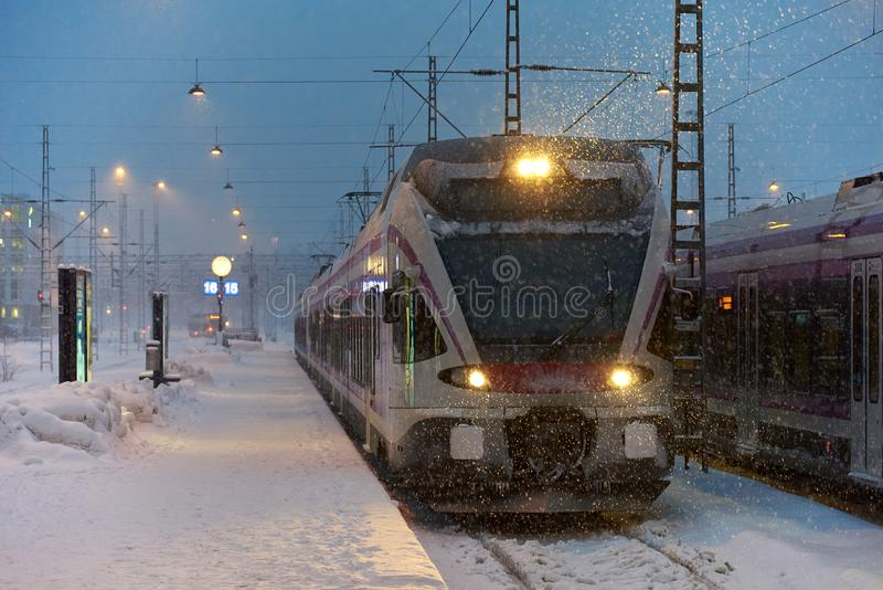 A local commuter train arriving at the Helsinki central railway in heavy snow storm royalty free stock photos