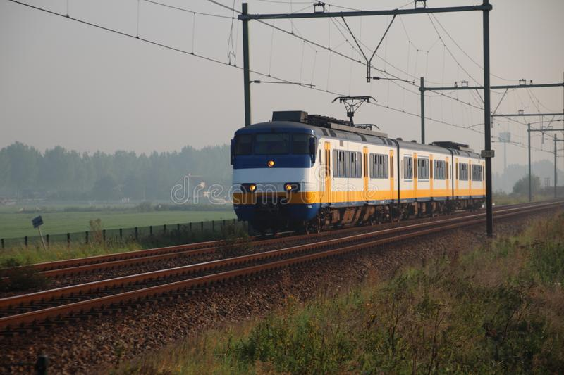 Local commuter train on track between the meadows of Moordrecht stock photography