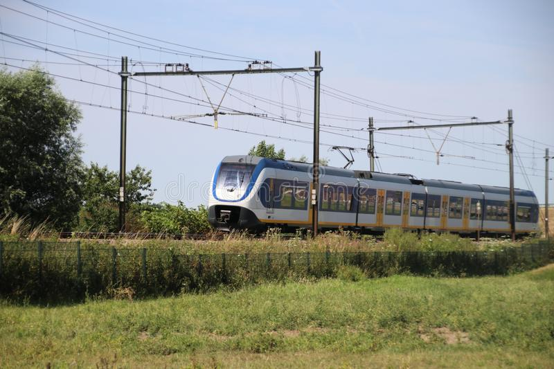 Local commuter train on the track at Moordrecht heading to Rotterdam in the Netherlands royalty free stock photography