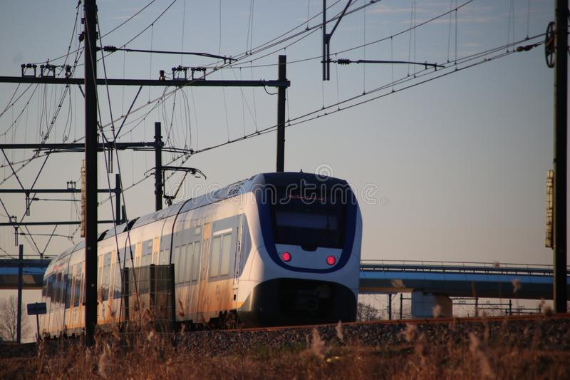 Local commuter type SLT of the NS at Moordrecht in evening sun between Den Haag and Gouda. royalty free stock photo