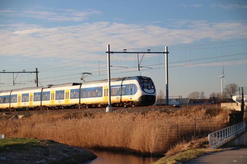 Local commuter type SLT of the NS at Moordrecht in evening sun between Den Haag and Gouda. royalty free stock image