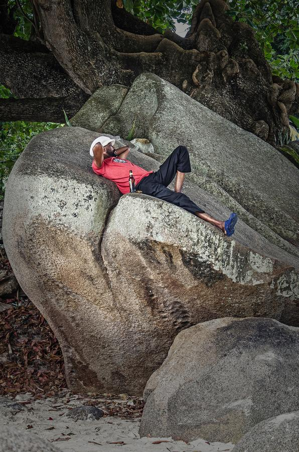 A local creole man lies ont he stone and drinks beer. Beau Vallon, Seychelles royalty free stock photography