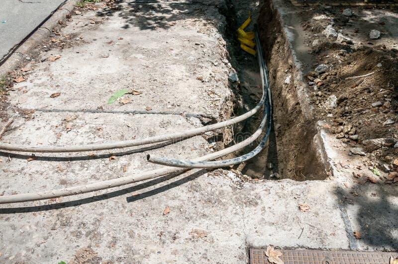 Local da reconstrução com a trincheira para linhas óticas do telefone subterrâneo fotografia de stock
