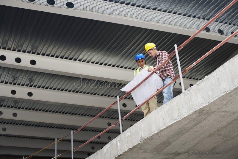 Local de Team With Building Plans At da construção imagem de stock