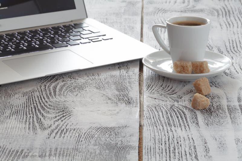 Local de trabalho com portátil e coffeecup no branco imagens de stock royalty free