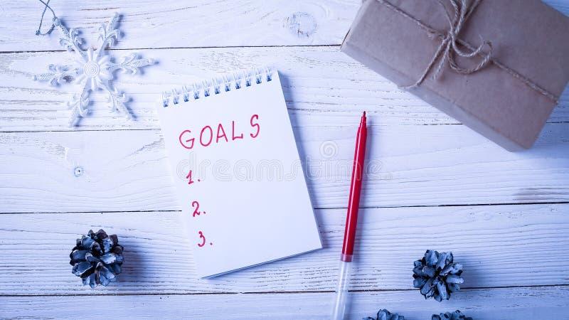 Local de trabalho com um diário, as decorações e os presentes Lista o do ` s do ano novo foto de stock