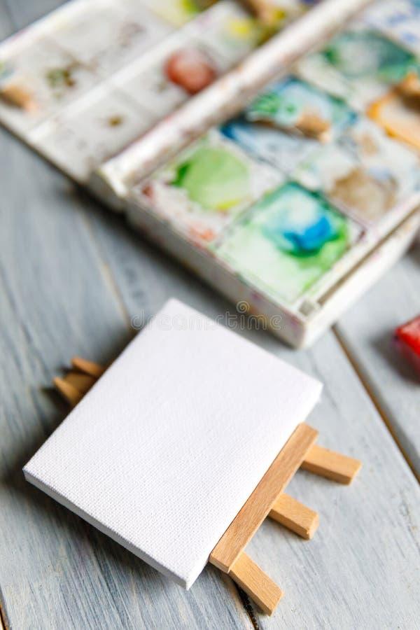 Local de trabalho do artista: Tabela branca de um artista com as ferramentas da arte para tirar imagens de stock