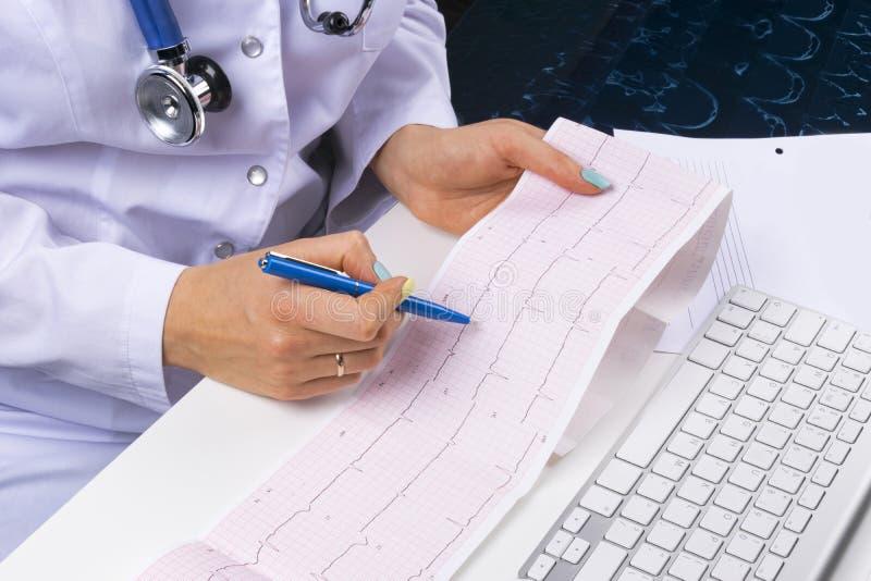 Local de trabalho do doutor Eletrocardiograma, ecg à disposição de um doutor fêmea com papel de gráfico do ekg na sala do escritó fotografia de stock royalty free