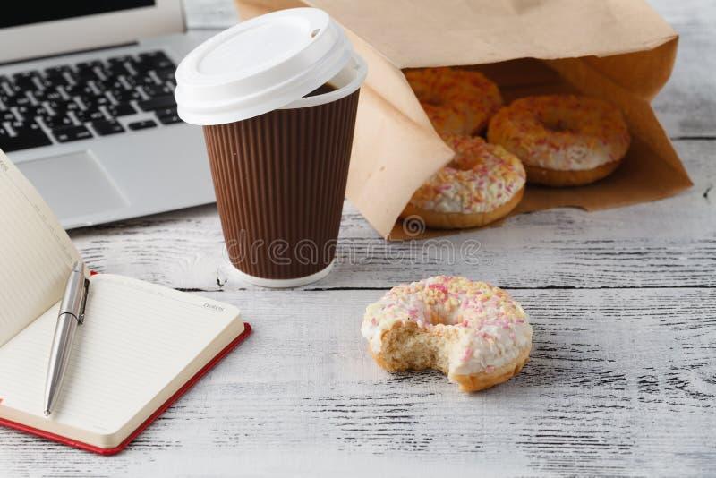 Local de trabalho do escritório com anéis de espuma e café do café da manhã imagens de stock royalty free
