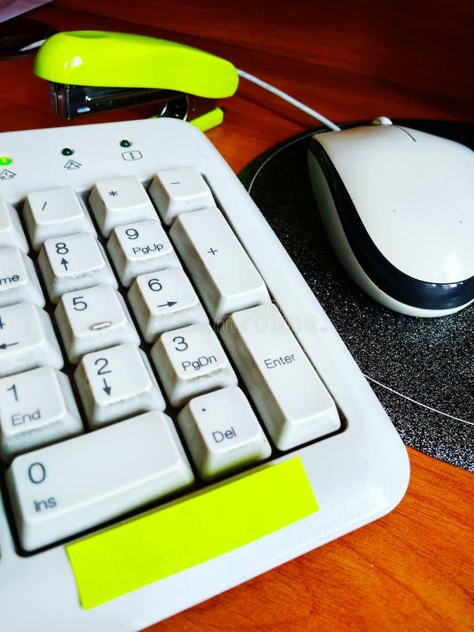 Local de trabalho do escritório com teclado, adesivos coloridos, mouse de computador e grampeador. Close-up na tabela fotos de stock royalty free