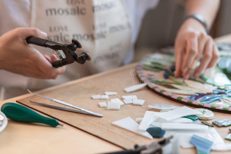 Local de trabalho do mestre do mosaico: o ` s das mulheres entrega a ferramenta de terra arrendada para detalhes do mosaico em pr fotos de stock