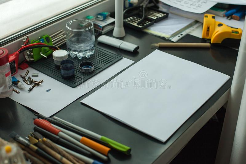 Local de trabalho do pintor na opinião lateral de ordem Mesa do desenhista com equipamento de desenho Estúdio home para o artista fotografia de stock