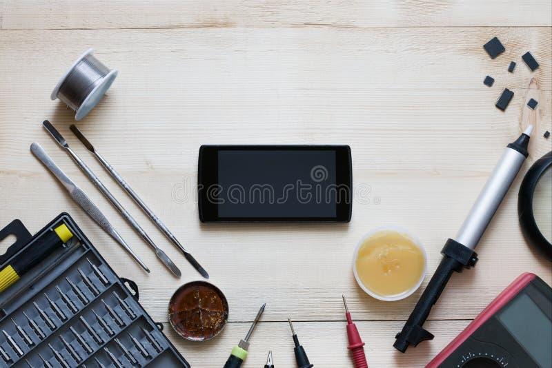 Local de trabalho do reparador com smartphone e as ferramentas especiais Jogo de ferramentas: multímetro, lupa, ferro de solda, r fotografia de stock royalty free