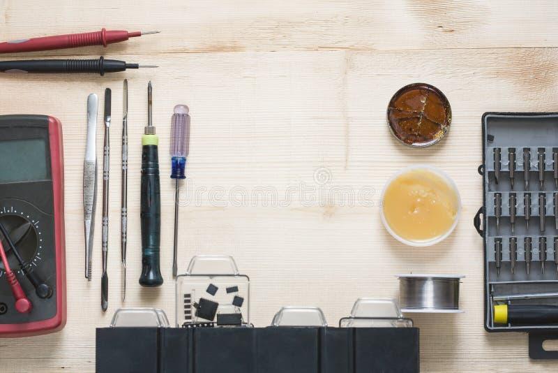 Local de trabalho do reparador com telefone e as ferramentas especiais Jogo de ferramentas: multímetro, lupa, ferro de solda, res fotografia de stock royalty free