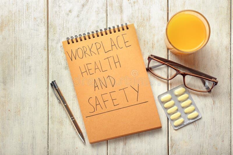 Local de trabalho, saúde e segurança escritos no caderno, vidro do suco de laranja e comprimidos das palavras no fundo de madeira imagens de stock