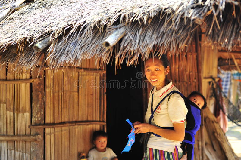 Local ethinic moman and kids. An ethinic minority woman and her kids in Laos, southeast Asia.Tribal culture,mountain lifestyle. Hut,thatch royalty free stock image