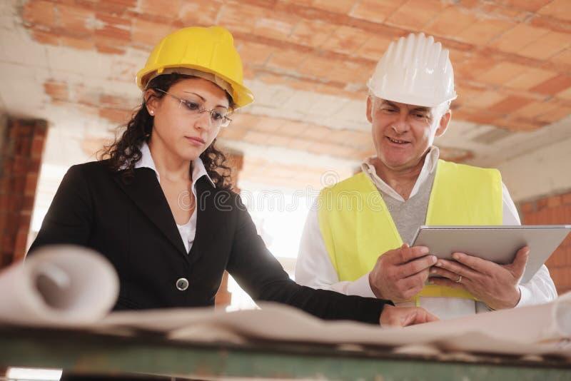 Local fêmea de Meeting In Construction do arquiteto e do contramestre foto de stock