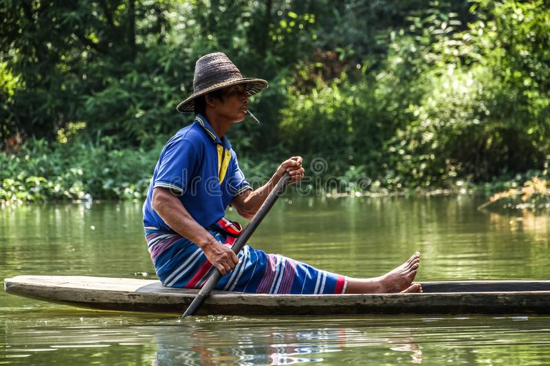 Local farmer paddling his traditional pirogue outside the sadan cave, Hpa-an, Hpa-an District, Myanmar stock photography