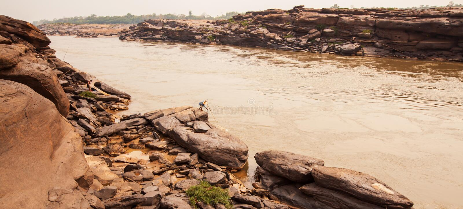 A local fisherman casting the fishing net in the Mekong River, fantastic scenery of steep by the river stock photography