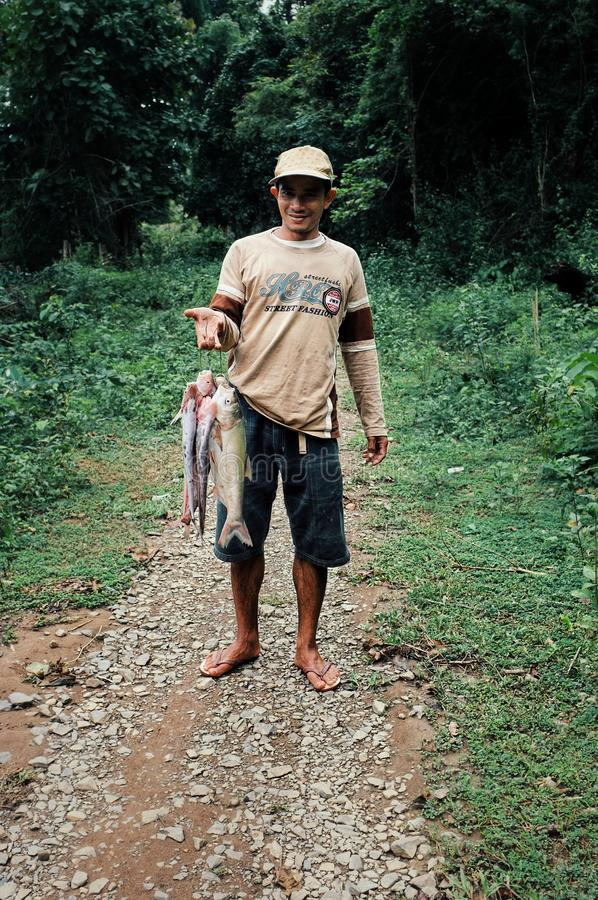local fisherman coming home with a catch on a jungle path stock images