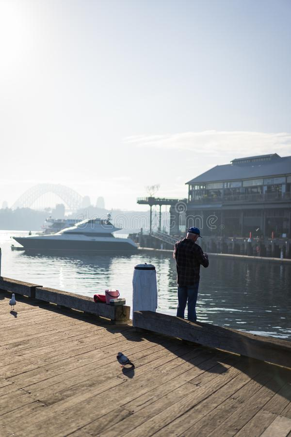 Local fisherman enjoys the early morning sun haze over the water at Pirrama Park/Jones Bay Wharf, Sydney NSW. June 2019 royalty free stock photography