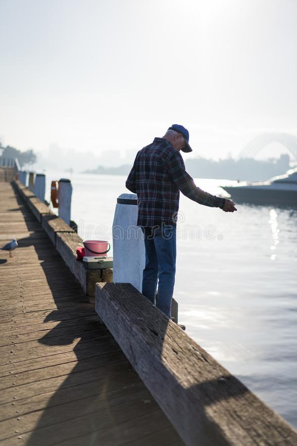 Local fisherman enjoys the early morning sun haze over the water at Pirrama Park/Jones Bay Wharf, Sydney NSW. June 2019. Taken from the boardwalk section of stock images
