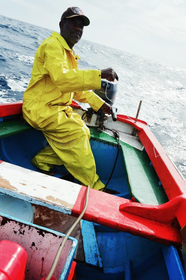 local fisherman going out to sea to fish for yellow fin tuna or wahoo in a traditional colorful dinghy royalty free stock image