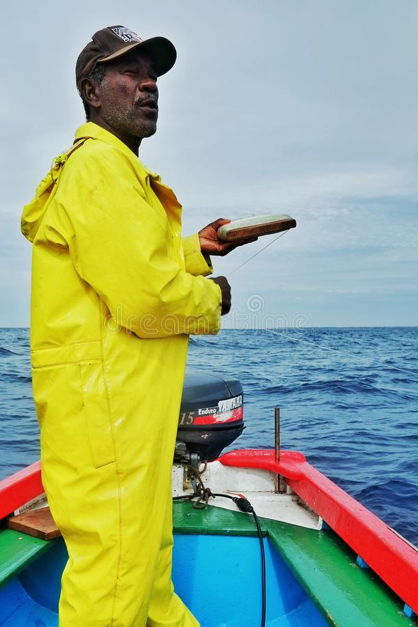 local fisherman going out to sea to fish for yellow fin tuna or wahoo in a traditional colorful dinghy royalty free stock images