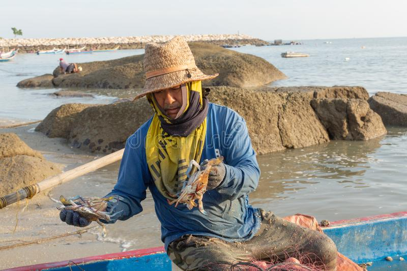 Local fisherman in his fishing boat,sorting his morning catch of crab. Tanjung Tokong Beach, Penang Island, Malaysia: December 25, 2018: Local fisherman in his stock image