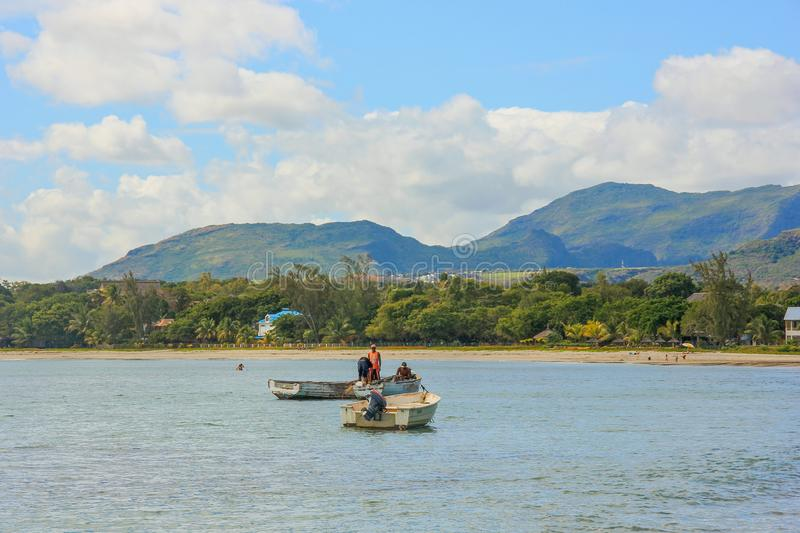 Local fishermen on old wooden boats fish in bay near small village. Surrounded by tropical greenery with beautiful coastline,cozy sandy beach against backdrop stock image