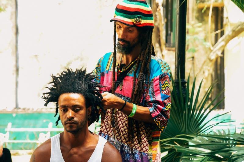 A local getting his hair styled in Havana, Cuba. A local getting his hair styled in the streets of Havana, Cuba stock photo