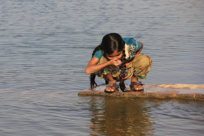 Local girl drinking from water reservoir, Khichan village, India. Local girl drinking from water reservoir, Khichan village, Rajasthan, India stock images