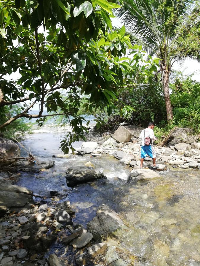 Local guide crossing the river in Agbalala Falls royalty free stock images