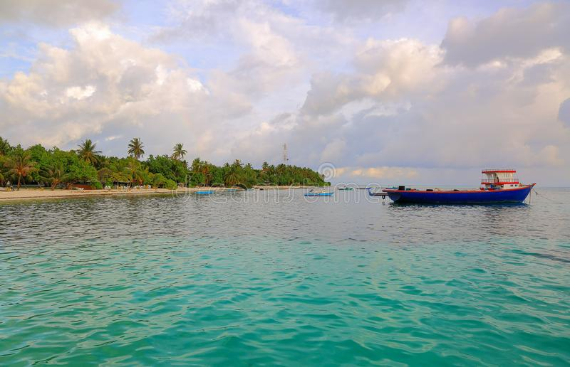 Local harbor in Indian Ocean, Maldives. Dhangethi Island. Small boats on turquoise ocean water on blue sky with white clouds backg. Round royalty free stock photo