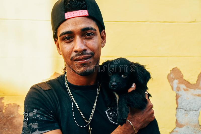 A local with his puppy posses for the camera in Trinidad, Cuba. A local with his young little puppy posses for the camera in Trinidad, Cuba stock images